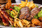 Platter of mixed meats, salad and French fries — Stok fotoğraf