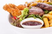 Platter of mixed meats, salad and French fries — ストック写真