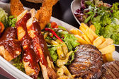 Platter of mixed meats, salad and French fries — Stock Photo