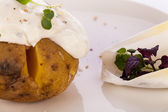 Baked jacket potato with sour cream sauce — Stock Photo