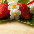 Stock Photo: Grouped strawberries on green leaves