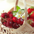 Red fruits with flowers in basket — Stock Photo