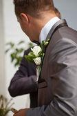 Brudgummen med blomma och pengar på bröstet — Stockfoto