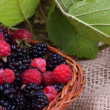 Stock Photo: Blackberry and raspberry with leaves in basket
