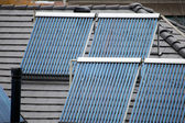 Four solar thermal tubes on rooftop — Stockfoto