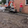 Stock Photo: Mini digger excavating driveway
