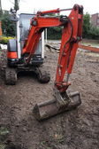 A mini digger excavating a driveway — Stock Photo