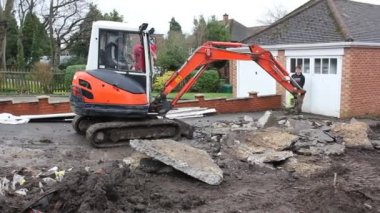A mini digger excavating a driveway — Stock Video