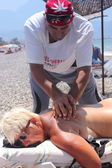 Masseur giving a full massage to a beautiful woman on the beach — Stock Photo