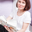 Girl with a book reading and waiting for guests — Stock Photo