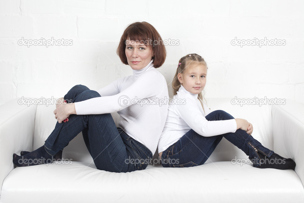 Mother with the daughter sit on a sofa in identical clothes  Stock Photo #19045007