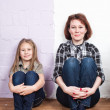 Mother with the daughter in jeans and a shirt sit on a floor against a wall from two flowers — Stock Photo