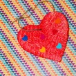 Royalty-Free Stock Photo: Multicolored paper hearth on a wooden red heart
