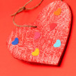 Royalty-Free Stock Photo: Multicolored paper hearths on a wooden red heart