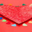 Multicolored paper hearths around a wooden red heart — Stock Photo #17994935