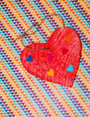 Multicolored paper hearth on a wooden red heart — Zdjęcie stockowe
