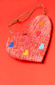 Multicolored paper hearths on a wooden red heart — Stock Photo