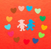 Multicolored paper hearths around multicolored paper boy and girl — Stock Photo