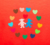 Multicolored paper hearths around multicolored paper boy and girl with hearth — Stock Photo