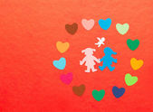 Multicolored paper hearths around multicolored paper boy and girl with angel — Stock Photo