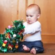 Baby boy playing with christmas tree — Stock Photo #18134009