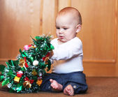 Baby boy playing with christmas tree — Stock Photo