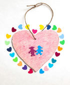 Multicolored paper hearths with a wooden pink heart and paper boy and girl — Stock Photo