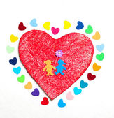 Multicolored paper hearths on a wooden red heart and paper boy and girl — Stock Photo