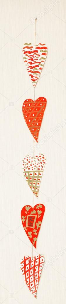 Wooden multicolored hearts hanging in line on white — Stock Photo #18484211