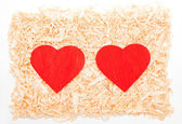Red hearts in the sawdust — Stock Photo