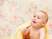 Baby crying in a yellow towel — Stock Photo