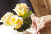 Hands and rings with rose bouquet — Stock Photo