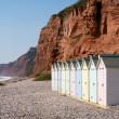 Beach huts and sandstone cliffs Budleigh Salterton Devon — Stock Photo