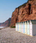 Beach huts and sandstone cliffs Budleigh Salterton Devon — Stock Photo