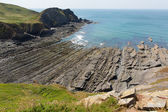 Rock strata on rocky beach cove with blue sea — Stock Photo