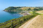 Coast path Talland Bay shingle beach between Looe and Polperro Cornwall England UK on a beautiful blue sly sunny day — Stock Photo