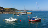 Brightly coloured boats in harbour with blue sea — Stock Photo