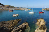 Boats in English harbour with blue sea — Stock Photo