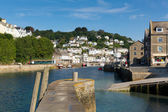 Looe harbour wall and town Cornwall England with blue sea — Stock Photo