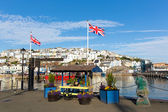 Colourful flowers and union jack flags at harbourside Brixham harbour Devon with blue sky and white clouds — Stock Photo