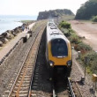 图库视频影像: Fast train approaching on coast at Dawlish Warren Devon