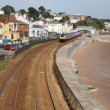 Train approaching from coast railway station bordering sand and sea Dawlish Devon England — Wideo stockowe