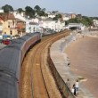 Train travelling away from camerviewed from bridge on railway bordering sand and seDawlish Devon England — стоковое видео #31641929