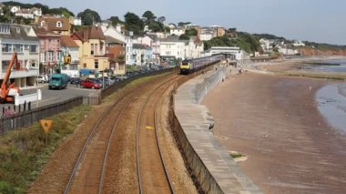 Train approaching from coast railway station bordering sand and sea Dawlish Devon England — Stock Video