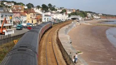 Train travelling away from camera viewed from bridge on railway bordering sand and sea Dawlish Devon England — Stock Video