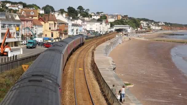 Tren viaja fuera de cámara vista desde el puente de ferrocarril que bordea el mar y arena dawlish devon Inglaterra — Vídeo de stock