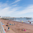 Holidaymakers on Teignmouth beach by pier Devon England — Stock Photo