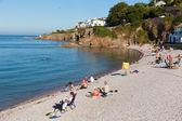 Tourists on Brixham breakwater beach Devon England UK in summer with blue sky — Stock Photo