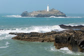 Lighthouse and island with sea breaking over rocks Godrevy Cornwall England UK — Stock Photo