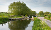 English countryside scene with canal and lock gates — Stock Photo
